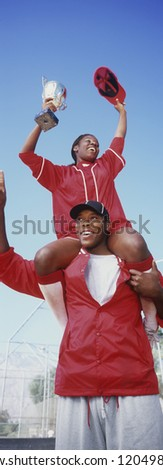 Low angle view cheerful African American baseball players with trophy against clear sky - stock photo