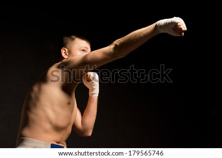 Low angle view in darkness of a fit young boxer throwing a right hook punch with an extended arm - stock photo