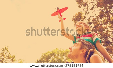Low angle view of a boy with toy aeroplane sitting on fathers shoulders at the park - stock photo