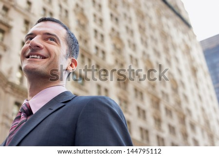 Low angle view of a businessman smiling against blurred building - stock photo
