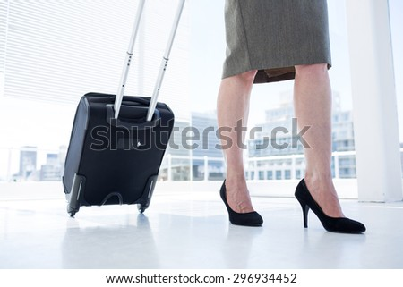 Low angle view of a businesswoman pulling her suitcase in the office