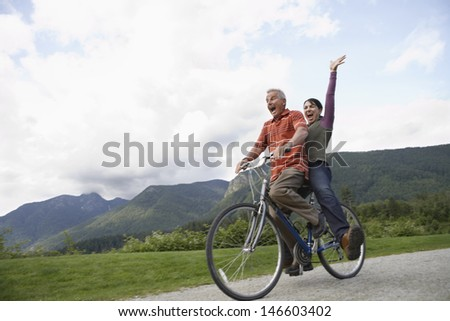 Low angle view of a cheerful middle aged couple riding bicycle on country road - stock photo