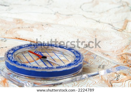 Low angle view of a compass on a topographic map - stock photo