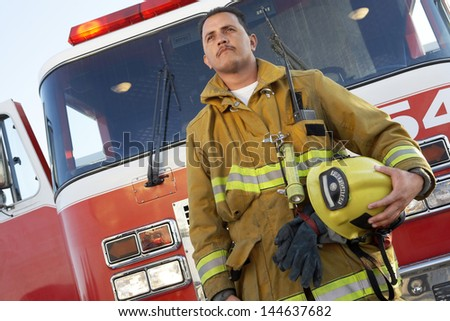 Low angle view of a confident Fire fighter standing in front of fire engine - stock photo