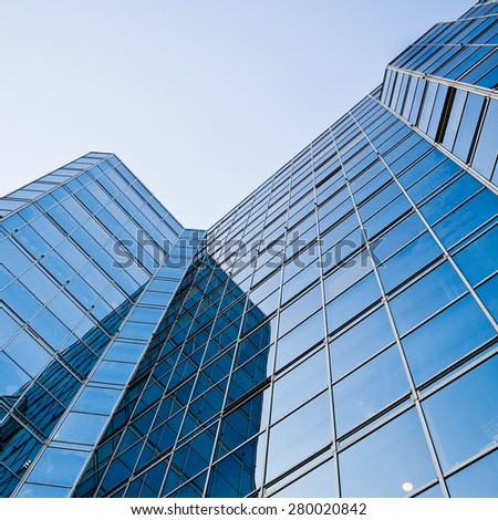 Low angle view of a contemporary glass and steel office skyscraper reflecting the clear blue sky above; square composition with copy space.