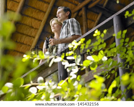 Low angle view of a couple on terrace with binoculars - stock photo