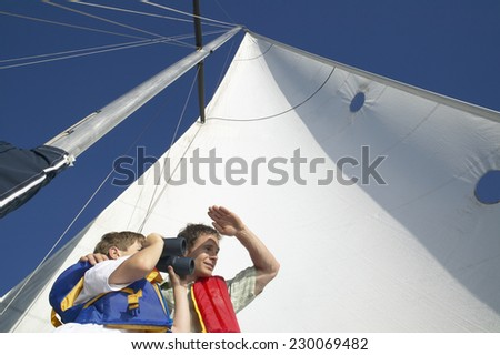 Low angle view of a father and his son standing at the end of a boat in lifejackets looking out to sea - stock photo