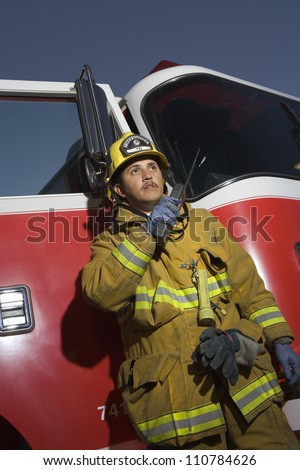 Low angle view of a firefighter talking on radio with fire truck in the background - stock photo
