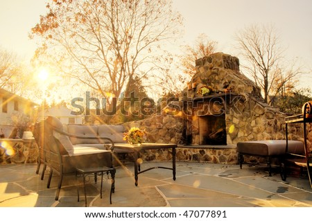 Low-angle view of a flagstone patio with an outdoor stone fireplace and furniture. Rays of sunlight stream down. Horizontal format. - stock photo