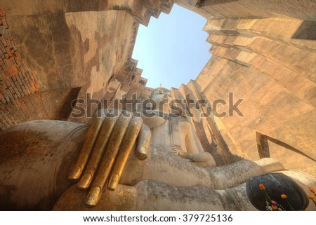 Low angle view of a giant ancient Buddha statue in Temple Wat Si Chum in Sukhothai Historical Park, Thailand ~ A huge sitting Buddha image with the posture of Subduing Mara inside a buddhist shrine - stock photo