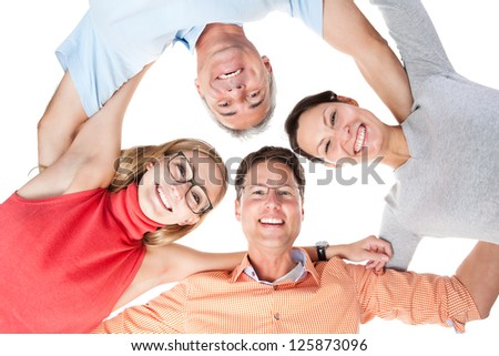 Low angle view of a group of happy middle aged friends with joyful smiles standing arm in arm looking down at the camera - stock photo