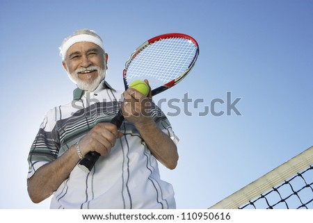 Low angle view of a happy senior man holding tennis racquet and ball against sky - stock photo