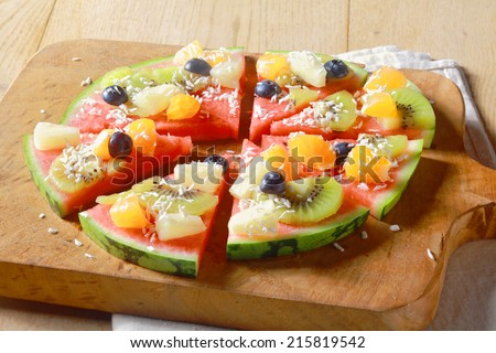 Low angle view of a healthy vegetarian and vegan tropical fruit watermelon pizza topped with kiwifruit, blueberries, orange, pineapple, and sprinkled with dried coconut, cut into segments for serving - stock photo