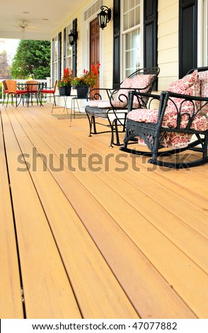 Low angle view of a large front porch with furniture and potted plants. Vertical format. - stock photo