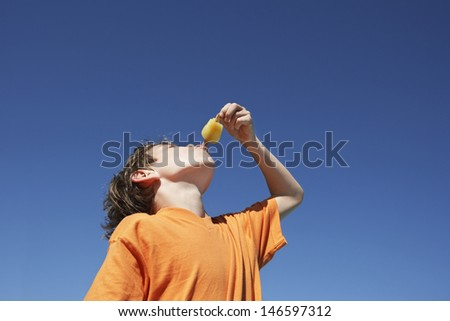 Low angle view of a little boy eating popsicle against clear blue sky - stock photo