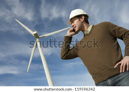 Low angle view of a male engineer using cell phone against wind turbine and cloudy sky