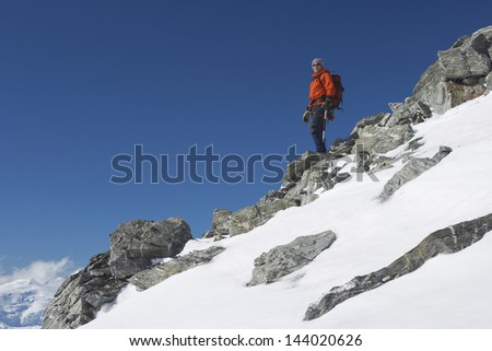 Low angle view of a male mountain climber descending snow and boulder slope - stock photo