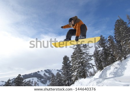 Low angle view of a male snowboarder jumping over snow covered hill against the sky - stock photo
