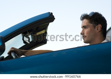 Low angle view of a man driving his convertible car - stock photo