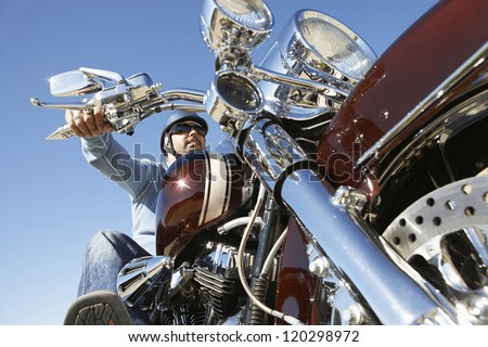 Low angle view of a man riding bike against clear sky - stock photo