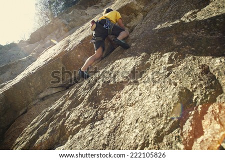 Low angle view of a man rock climbing a vertical cliff - stock photo