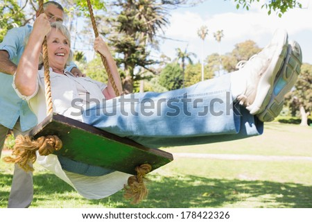 Low angle view of a mature couple at swing in the park - stock photo