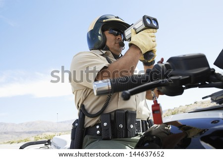 Low angle view of a police officer looking through radar gun - stock photo