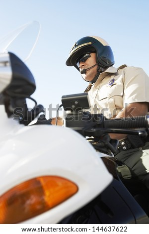 Low angle view of a police officer sitting on motorcycle against the sky