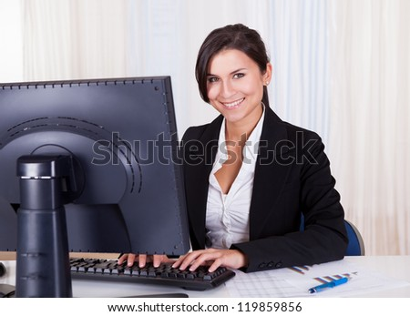 Low angle view of a relaxed smiling beautiful businesswoman sitting behind her desk working at her computer - stock photo