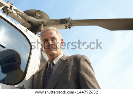 Low angle view of a serious middle aged businessman by helicopter  - stock photo