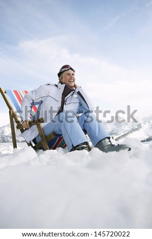 Low angle view of a smiling woman sitting on deckchair in snowy mountains - stock photo
