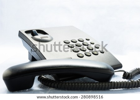 Low angle view of a white office dial up landline or terrestrial telephone with handset and keypad for telephonic communication - stock photo