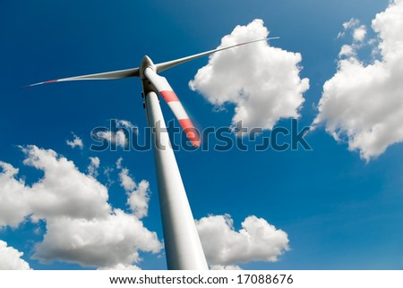 low angle view of a wind turbine against a blue sky full of white clouds - stock photo