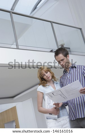 Low angle view of a young couple observing plan in new home - stock photo