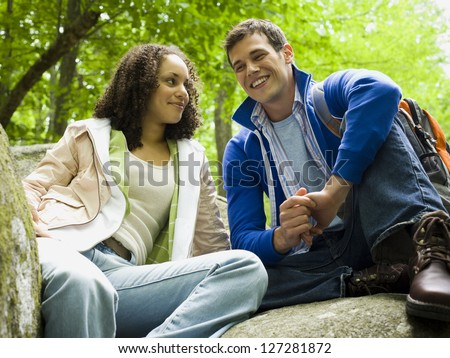 Low angle view of a young couple sitting on a rock