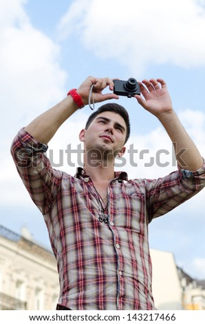 Low angle view of a young man taking a photograph with a compact camera against a cloudy blue sky - stock photo