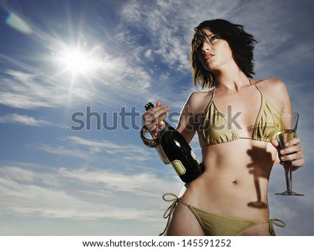 Low angle view of a young woman in bikini holding champagne against the sky - stock photo