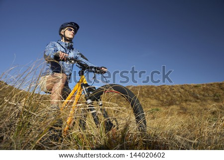 Low angle view of a young woman riding bicycle in field against clear blue sky - stock photo