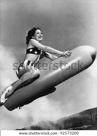 Low angle view of a young woman sitting on a rocket and smiling