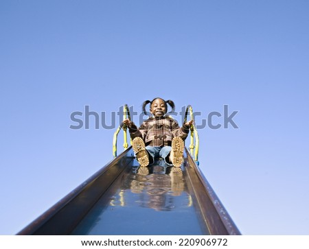 Low angle view of African girl at top of slide - stock photo