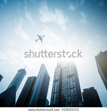 low angle view of airplane flying over skyscrapers,shanghai china.