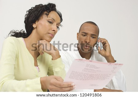 Low angle view of an African American couple reading document - stock photo