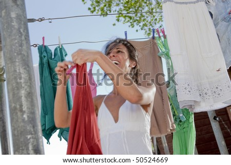 Low angle view of an attractive young woman hanging laundry to dry on a clothesline. Horizontal format. - stock photo