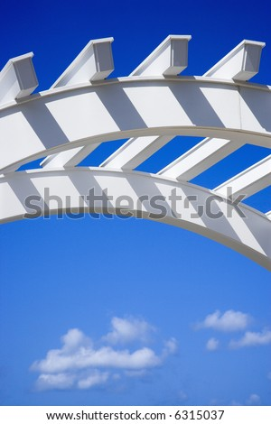 Low angle view of arched white arbor with blue sky. - stock photo