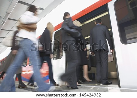 Low angle view of business commuters getting into a train - stock photo