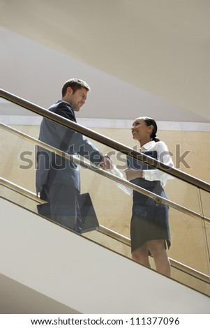 Low angle view of business people greeting each other on staircase