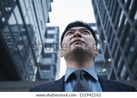Low angle view of businessman outdoors in Beijing - stock photo
