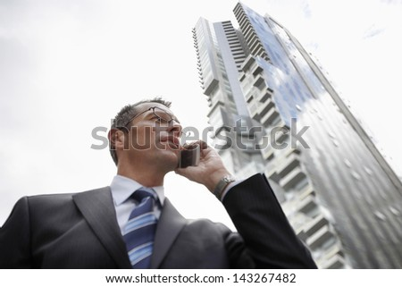 Low angle view of businessman using mobile phone against tall building - stock photo