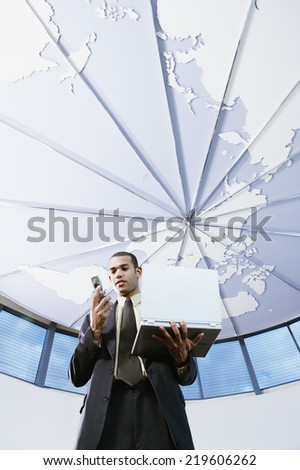 Low angle view of businessman with cell phone and laptop - stock photo