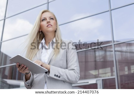 Low angle view of businesswoman holding digital tablet while looking away against office building - stock photo